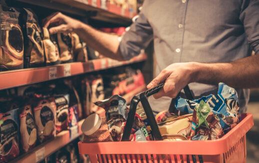homem fazendo compras em um supermercado segurando