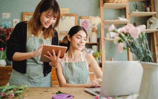 duas mulheres empresárias uma olhando para um tablet e outra para um notebook