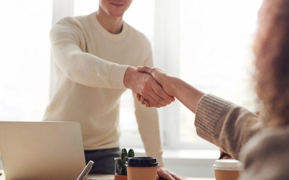 Duas pessoas apertando as mãos fechando um negócio