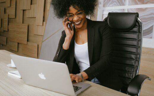 mulher empresária negra sorrindo sentada trabalhando