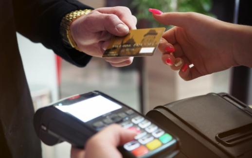 duas mãos, uma recebendo um cartão de crédito para realizar um pagamento em uma maquineta